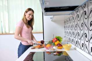 one happy young woman with apple in kitchen and other food and vegetables