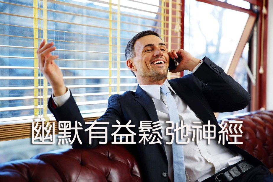 Laughing businessman sitting and talking on the phone at office