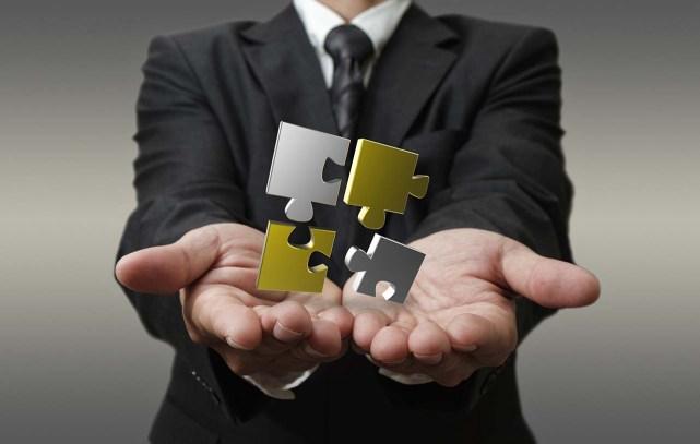 business man shows 3d metallic puzzle as concept